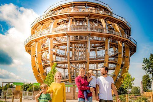 Familie mit Holzkugel im Hintergrund
