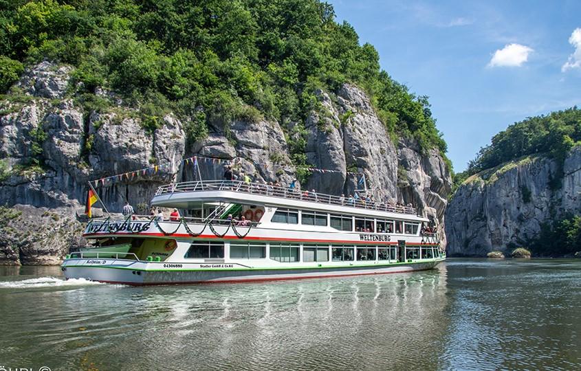 Schiff Weltenburg auf Fluss mit Steinwänden im Hintergrund